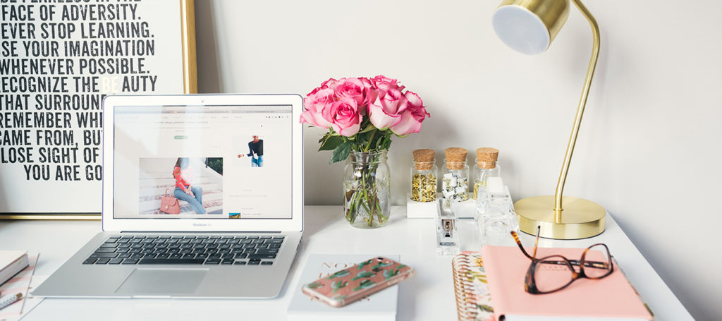 white table with laptop, lamp, and flowers - importance of blogs on websites