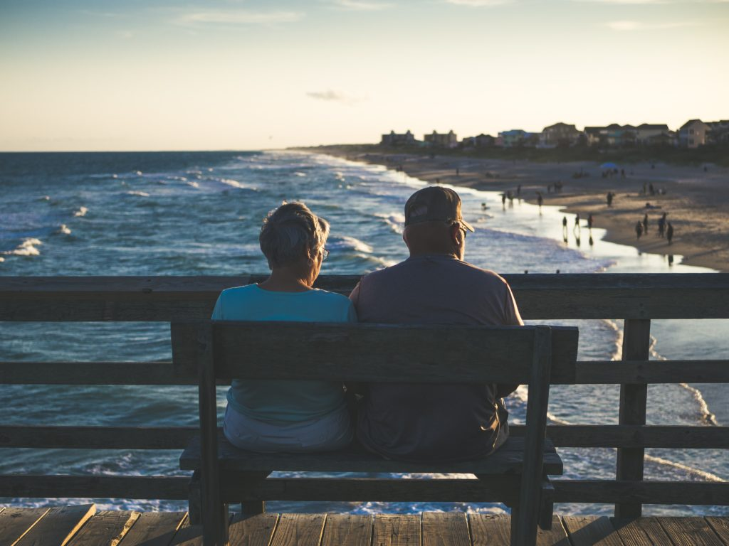 older man and woman sitting on an ocean pier - health benefits of CoQ10